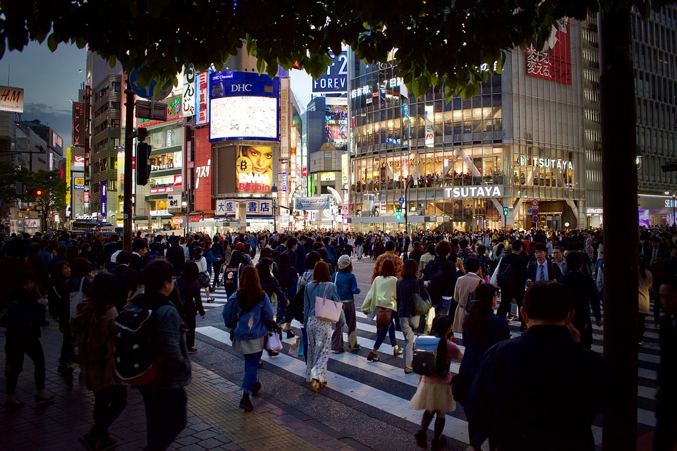 Tokyo downtown street covered with people that are walking in all directions.